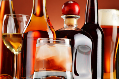 tomando vino: Botellas y vasos de bebidas alcoh�licas surtidos.