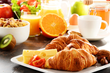 croissant: Breakfast consisting of fruits, orange juice, coffee, honey, bread and egg. Balanced diet.