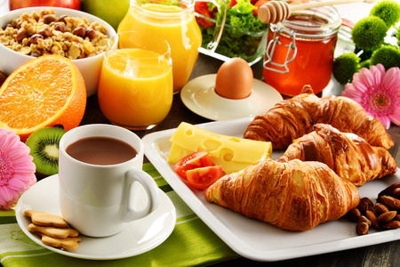 Breakfast consisting of fruits, orange juice, coffee, honey, bread and egg. Balanced diet.