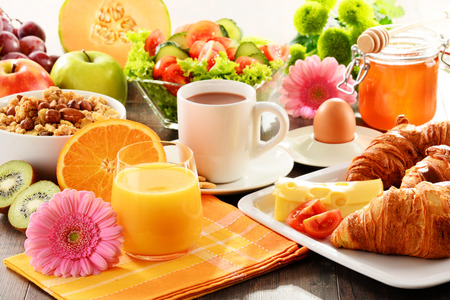 egg cups: Breakfast consisting of fruits, orange juice, coffee, honey, bread and egg. Balanced diet.
