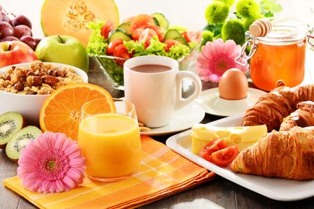 La colazione a base di frutta, succo d'arancia, caffè, miele, pane e uova. Dieta bilanciata.
