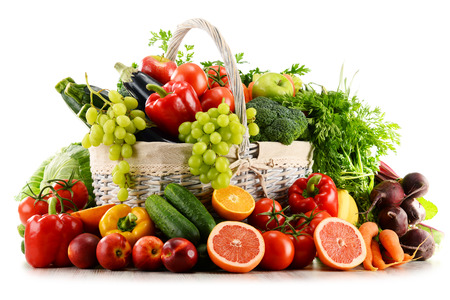 basket: Variety of organic vegetables and fruits in wicker basket isolated on white