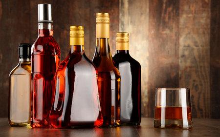 whisky bottle: Bottles of assorted alcoholic beverages.