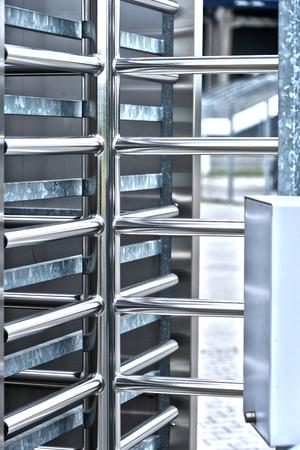 guarded: Full-height turnstile guarded stadium entrance. Revolving door