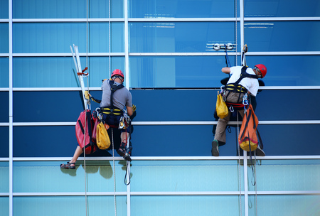 manual: Two construction workers working at height