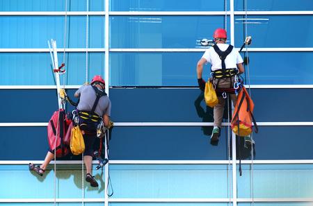 obreros trabajando: Dos trabajadores de la construcci�n que trabajan en la altura de rascacielos comercial moderna. Foto de archivo
