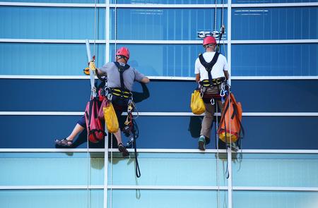 2 つの建設労働者は、近代的な商業ビルの高さで作業します。