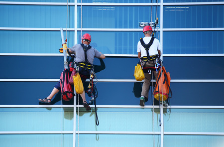 Two construction workers working at height on modern commercial skyscraper.