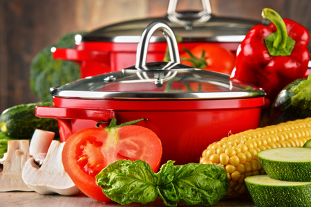 Composition with red steel pots and variety of fresh vegetables. Stockfoto