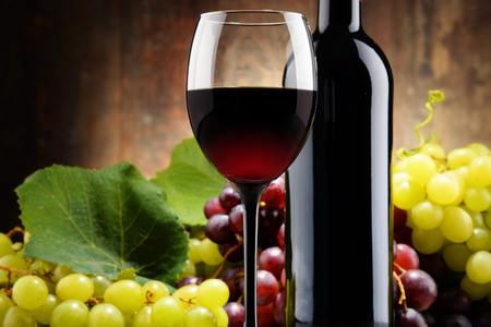 wine glass: Composition with glass, bottle of red wine and fresh grapes.
