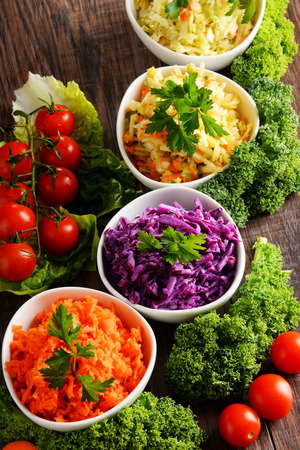ensalada de verduras: Composition with four vegetable salad bowls on wooden table.