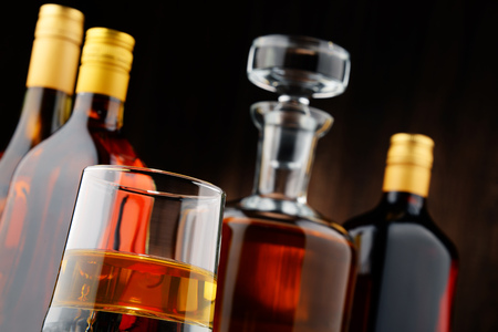 bebidas alcoh�licas: Composition with bottles of assorted alcoholic beverages and glass of whisky Editorial