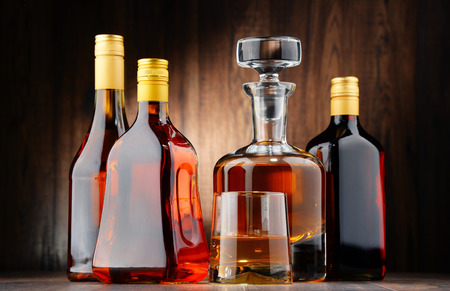 distilled alcohol: Composition with bottles of assorted alcoholic beverages and glass of whisky Editorial