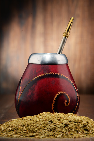 mate drink: Composition with yerba mate cup and leaves.