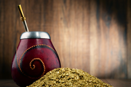 mate infusion: Composition with yerba mate cup and leaves.