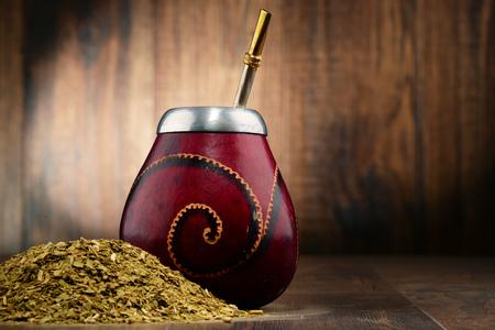 yerba mate: Composición con yerba mate y taza de hojas.
