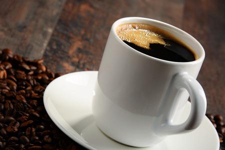 copa: Composición con taza de café y granos blancos.