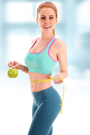 body shape: Young woman holding measure tape and apple. Weight loss.