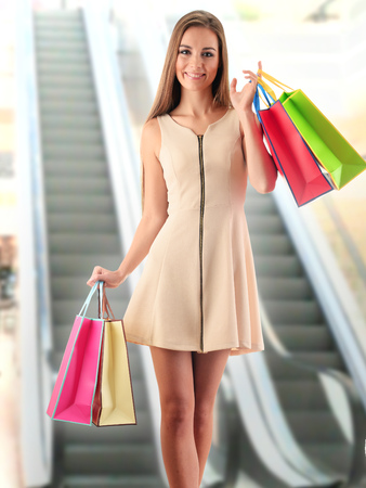 woman dress: Young woman with shopping bags in shopping mall