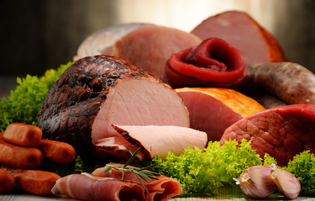 Assorted meat products including ham and sausages. Stockfoto