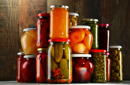 larder: Jars with pickled vegetables, fruity compotes and jams in cellar. Preserved food