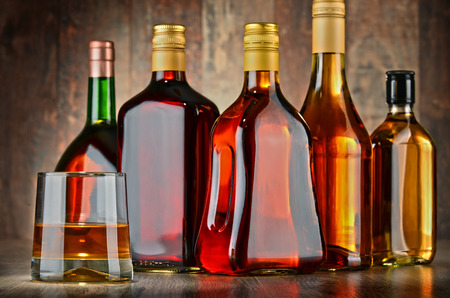 excise: Glass and bottles of assorted alcoholic beverages.