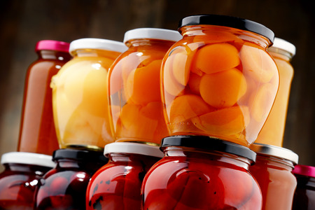 Jars with fruity compotes and jams. Preserved fruits. Stock Photo
