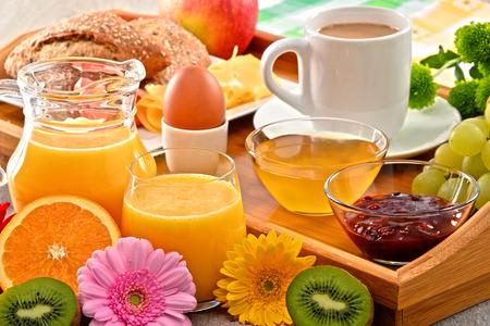 alimentacion balanceada: Desayuno en la bandeja servida con café, jugo de naranja, huevo, pan y miel. Dieta equilibrada.
