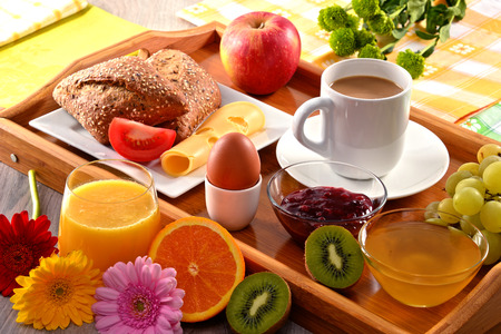 fruits juice: Breakfast on tray served with coffee, orange juice, egg, rolls and honey. Balanced diet.