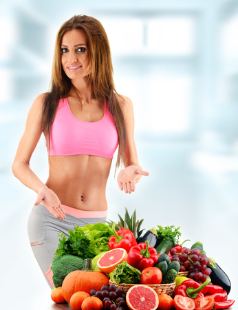 woman eating fruit: Young woman with variety of organic vegetables and fruits.
