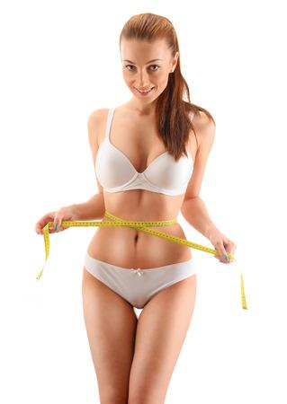 cintura perfecta: Mujer joven que se mide. La pérdida de peso.
