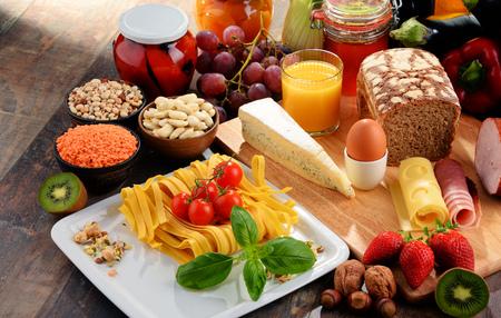 pan y vino: Composición con la variedad de productos alimenticios orgánicos en la mesa de la cocina