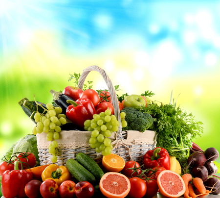 basket: Variety of organic vegetables and fruits in wicker basket