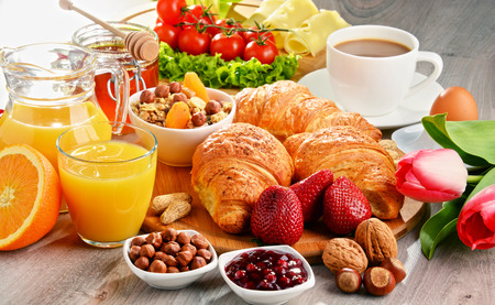 Breakfast consisting of croissants, coffee, fruits, orange juice, coffee and jam. Balanced diet. Standard-Bild