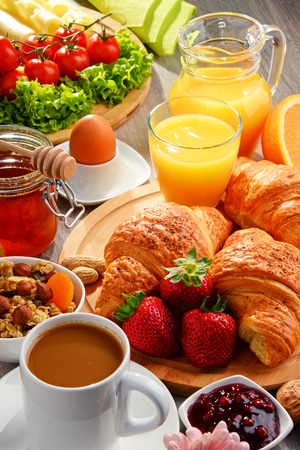 Breakfast consisting of croissants, coffee, fruits, orange juice, coffee and jam. Balanced diet. Foto de archivo