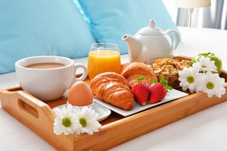 king size: Breakfast tray in bed in hotel room. Stock Photo