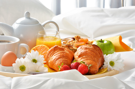 Breakfast tray in bed in hotel room. Archivio Fotografico