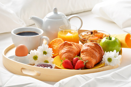 Breakfast tray in bed in hotel room. Stock Photo