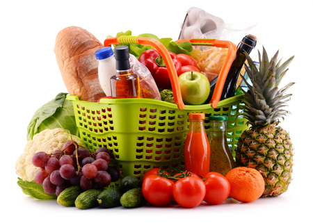 assorted: Plastic shopping basket with assorted gorcery products isolated on white