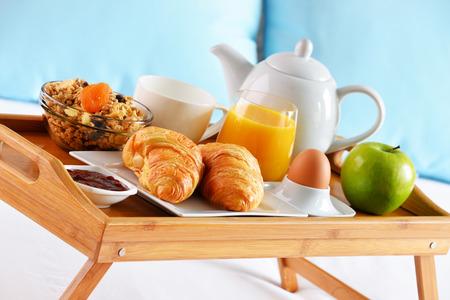 king size: Breakfast on tray in bed in hotel room.