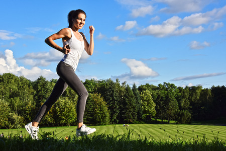 Young woman running in the park during sport training. Stock Photo