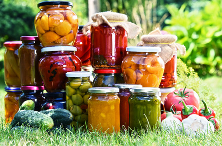 canned: Jars of pickled vegetables and fruits in the garden. Marinated food. Stock Photo