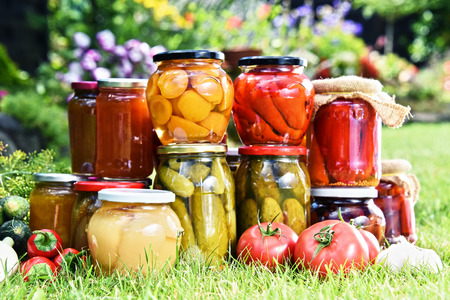 Jars of pickled vegetables and fruits in the garden. Marinated food. Stock Photo