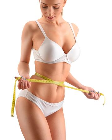 cintura: Mujer joven que se mide. La pérdida de peso.