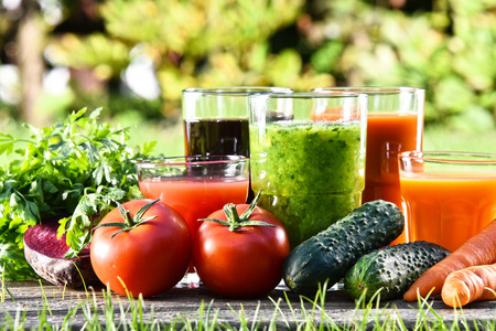 paleolithic: Glasses with fresh organic detox juices in the garden. Stock Photo