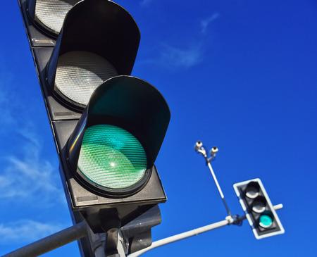 Traffic lights over blue sky. Green light Фото со стока