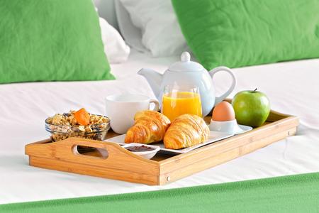 honey moon: Breakfast on tray in bed in hotel room.