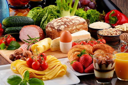 Composition with variety of organic food products on kitchen table