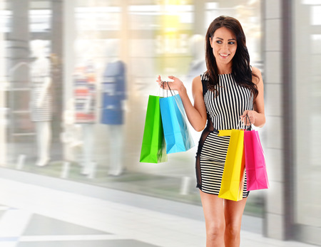 fashion style: Young woman with bags in shopping mall