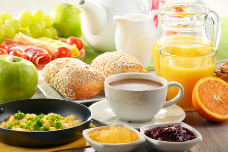 Breakfast served with coffee, orange juice, egg, rolls and honey. Balanced diet. Stock Photo